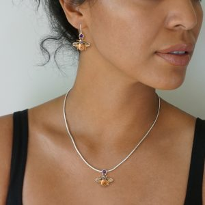 Model wearing matching bee earrings & pendant